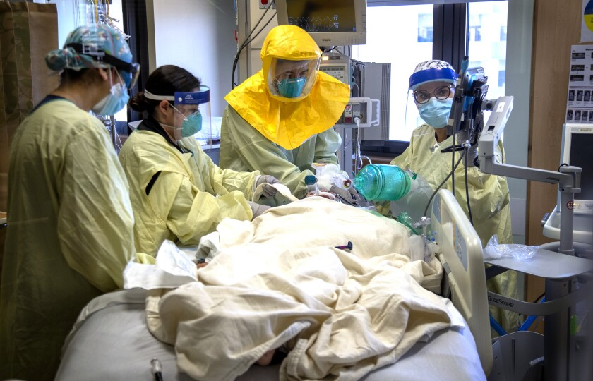 Hospital staff in protective masks, gowns and face shields work on a person lying on a hospital bed.