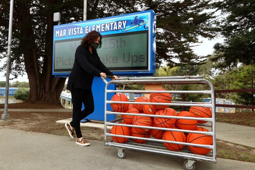 Kim Kaspar office assistant for Mar Vista Elementary rolls out a bin full of basketballs.