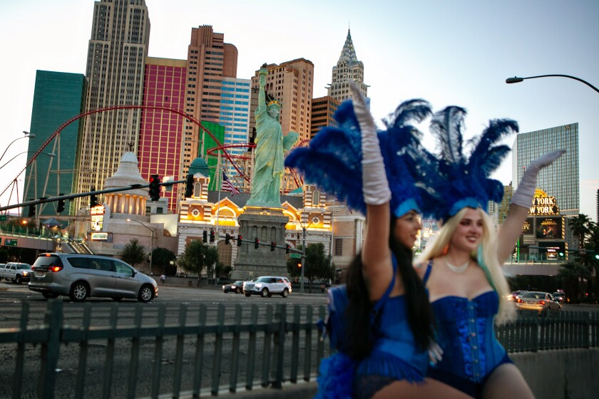 Two Vegas showgirls in blue outfits and feathered hats raise their arms in the air on the Strip