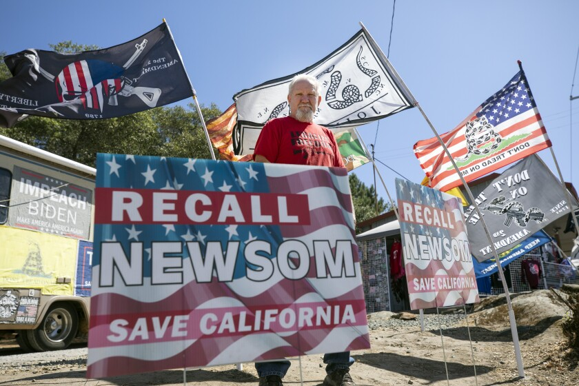 Recall Newsom volunteer Pat Miller holds up a sign during petition-signing event