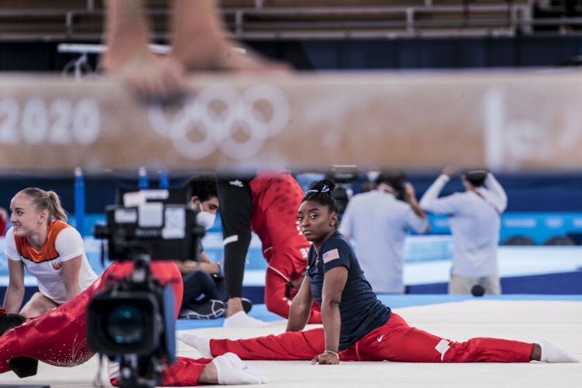 USA gymnast Simone Biles looks off as she warms up before competing in the Women's Balance Beam at Ariake Gymnastics Centre.