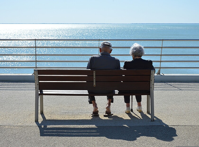 Two older adults sit on a bench near water.