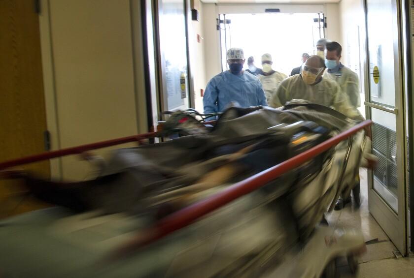 A hospital gurney streaks by, pushed by men wearing masks.