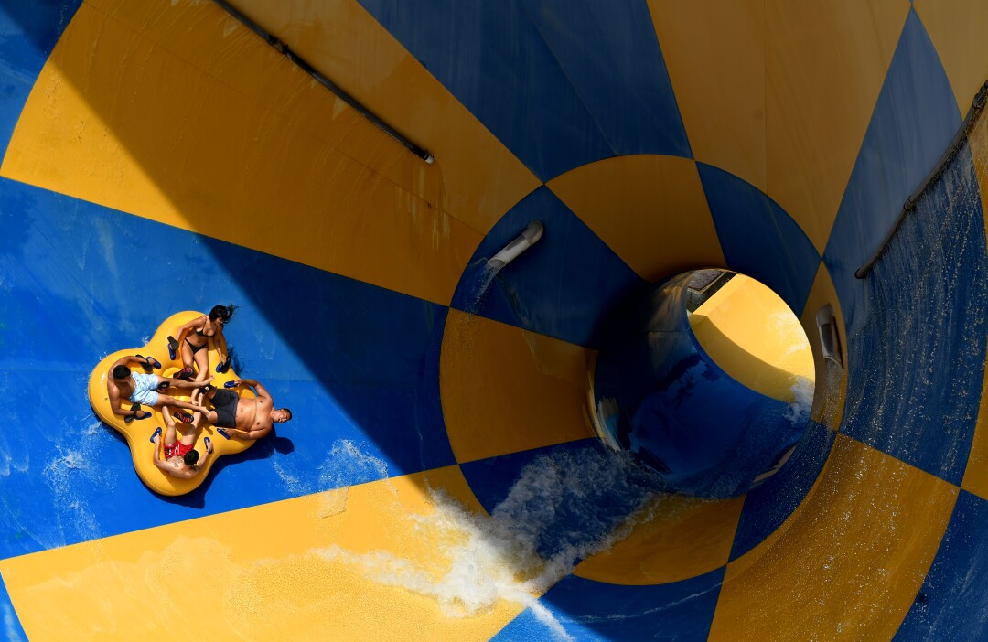 People enjoy a slide at Six Flags Hurricane Harbor water park in Valencia during the first day of California reopening.