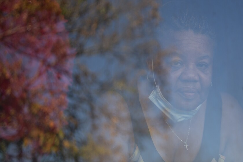 Deborah Bell-Holt looks out the window of her house in Jefferson Park near Downtown Los Angeles on Jan. 21, 2021. Photo by Shae Hammond for CalMatters