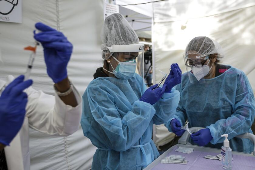 Nurse Cherry Costales, center, prepares a COVID-19 vaccine in Los Angeles