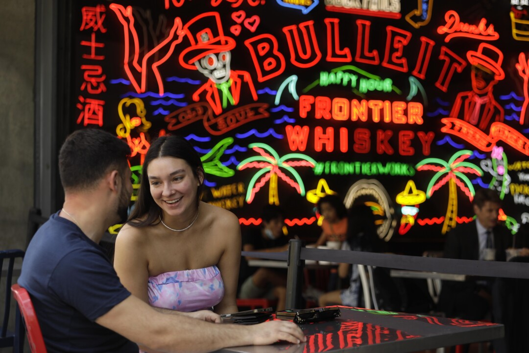 Two people talk in front of a large neon sign
