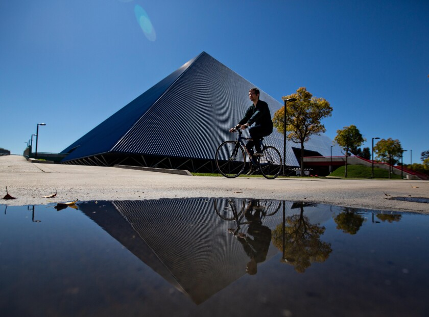 A student bikes past The Walter Pyramid at Cal State Long Beach