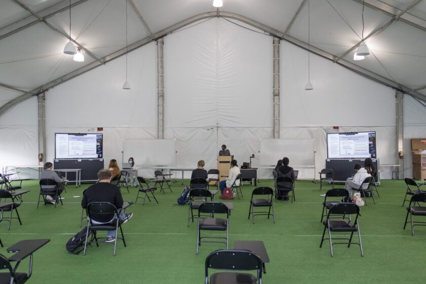 Students attend a genetics lecture in an outdoor tent at the University of California San Diego. Photo by Arlene Banuelos for CalMatters