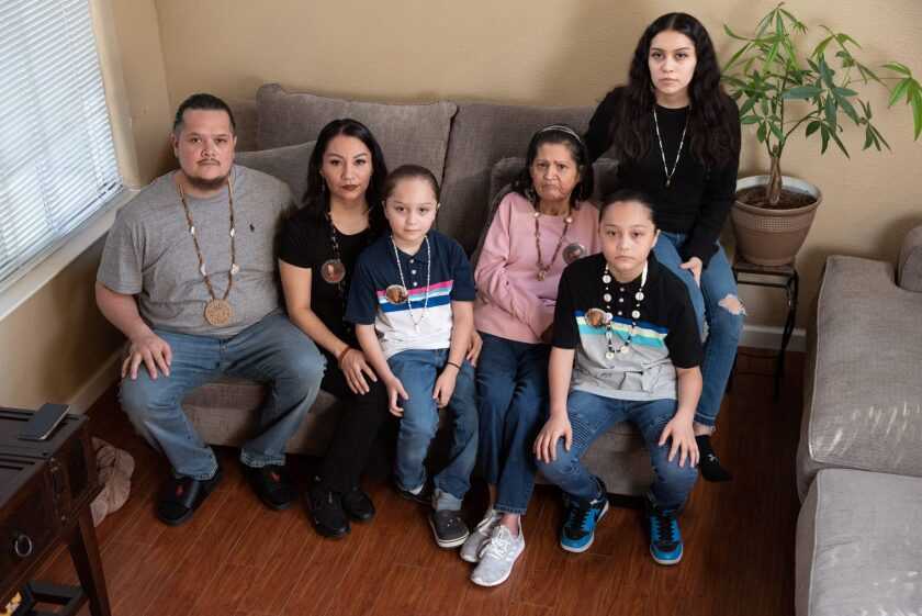 From left, Sergio Hinojosa Jr., Leticia Aguilar, Jordan Hinojosa, Jenny Sigala, Sergio Hinojosa III, and Angelina Hinojosa pose for a portrait in their home in Elk Grove on Friday February 26, 2021. Photo by Salgu Wissman for USA TODAY.