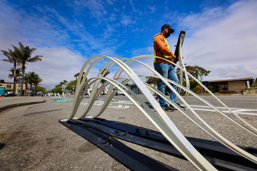 A county worker installs the wave delineators on Portola Drive in Pleasure Point.