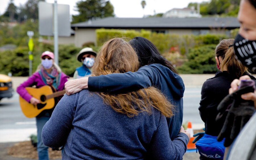 Friends, family and co-workers listen to Susan Moren, Vai Campbell's mom, play songs in her daughter's memory on Thursday.