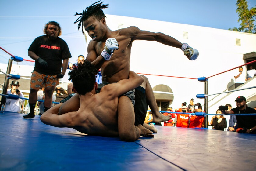 """Two men grapple on the mat as a man in stocking feet and a """"Backyard Squabbles"""" T-shirt stands nearby."""