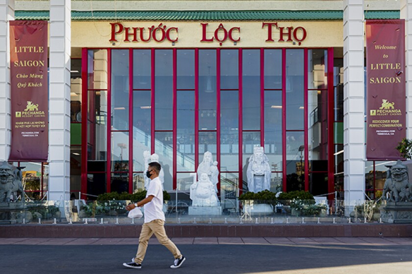 A person walks past Phước Lộc Thọ in the Little Saigon neighborhood in Westminster on Oct. 13, 2021. Photo by Deric Mendes for CalMatters