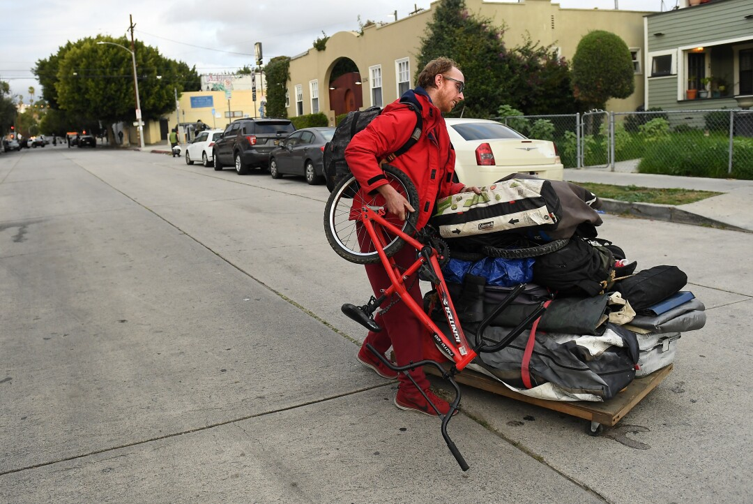 Charles McKnight moves his belongings along Logan St. before LAPD officers evict homeless from an encampment in Echo Park.