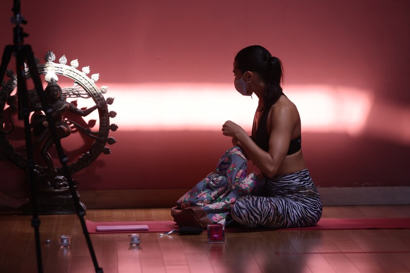 People practice yoga in studios for the first time in months after county moves to orange tier