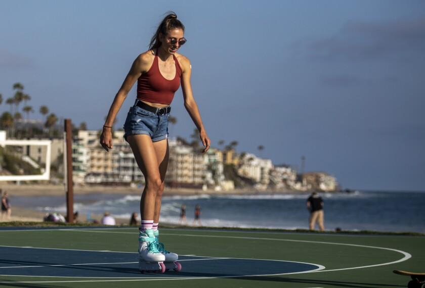 A woman roller-skates near the beach.