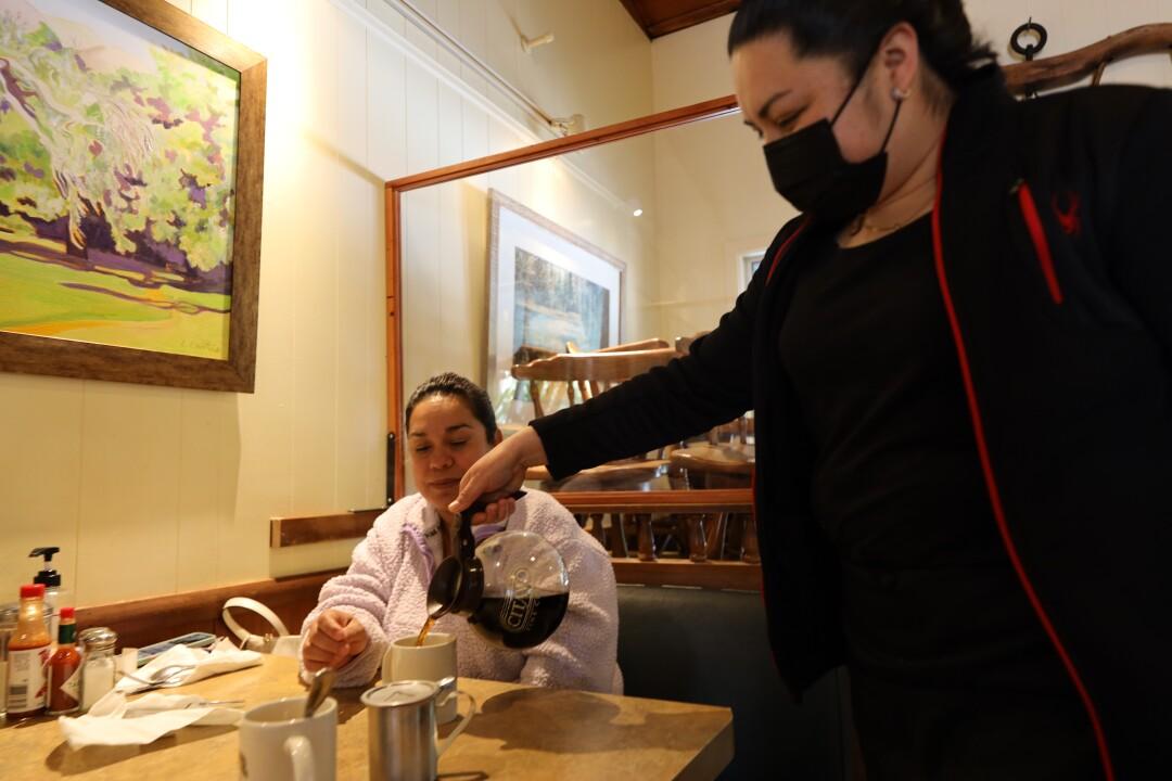 Busser Rocio Rameno pours customer Mayra Almanza a cup of fresh brewed coffee at Silver Spur Restaurant.