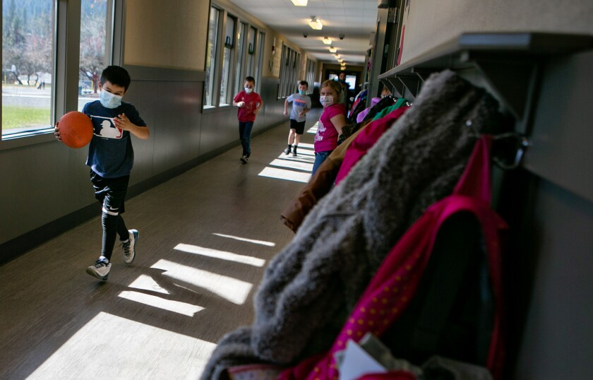 Kids wearing masks run to recess from inside their school.