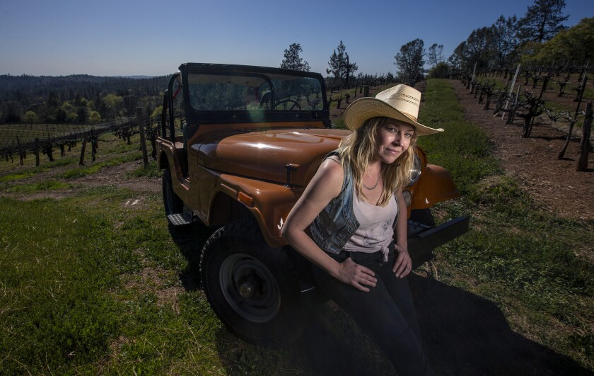 Woman sits on Jeep's bumper parked in front of rows of grapevines