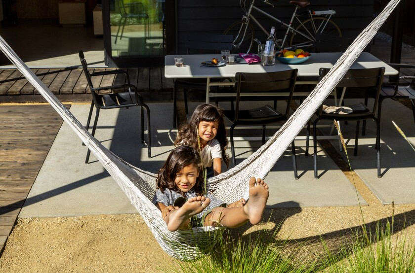 Two children play with a hammock on a patio.