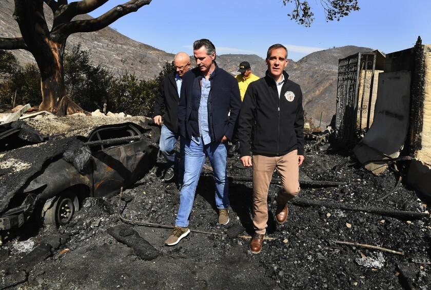 GOV. GAVIN NEWSOM, center, looks over the fire devastation in Brentwood with L.A. Mayor Eric Garcetti