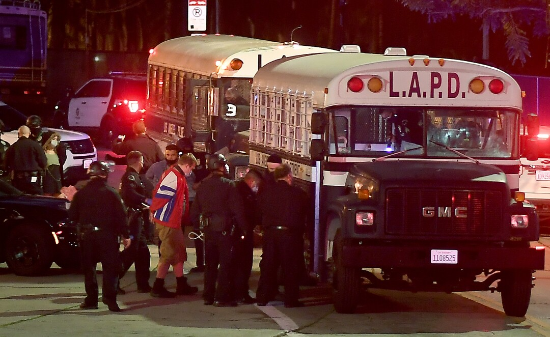 Protestors board an LAPD bus after being arrested in Echo Park Thursday night.