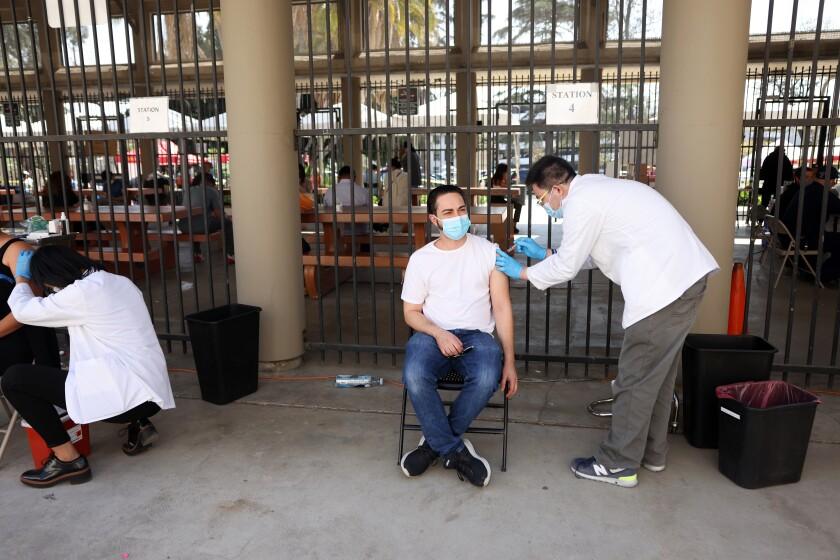 Artim Aghakhani receives a Johnson & Johnson inoculation