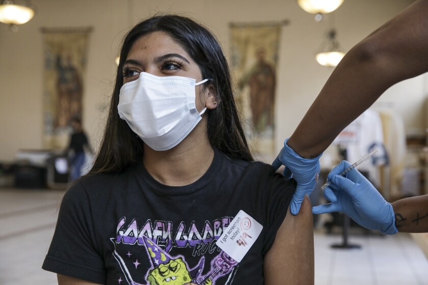 Los Angeles, CA - April 09: Cecy Gonzalez, 20, gets a COVID-19 vaccine at a vaccination clinic established by Councilman Curren Price in partnership with St. John's Well Child and Family Center at St. Patrick's Catholic Church on Friday, April 9, 2021 in Los Angeles, CA.(Irfan Khan / Los Angeles Times)