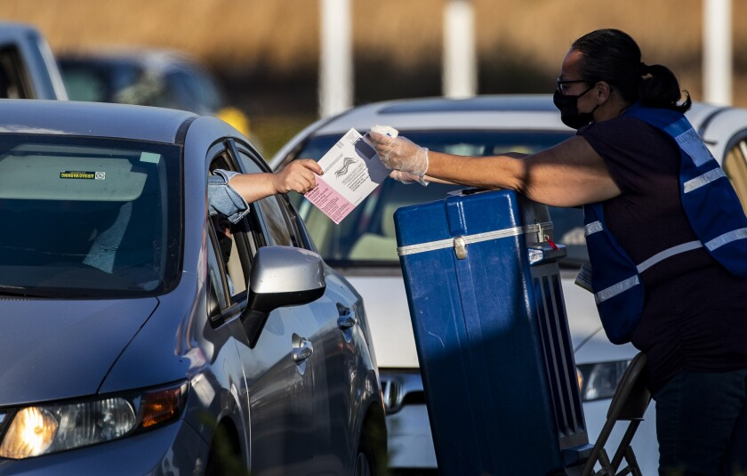 A voter hands her ballot to an election official to be dropped in a ballot box during a drive-thru ballot drop-off