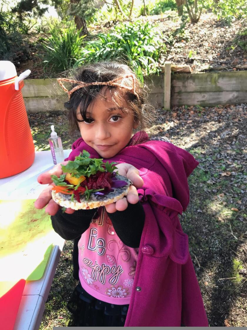Little girl holding a plate of salad she made