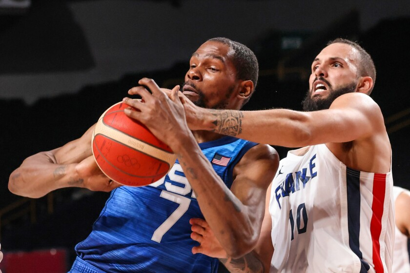 Team France shooting guard Evan Fournier knocks the ball from Team United States forward Kevin Durant