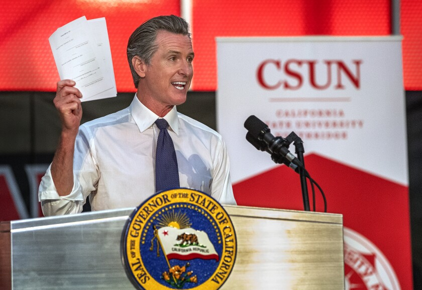 Gov. Gavin Newsom holds up some of the 7 bills he signed that are part of a $47.1 billion higher education package