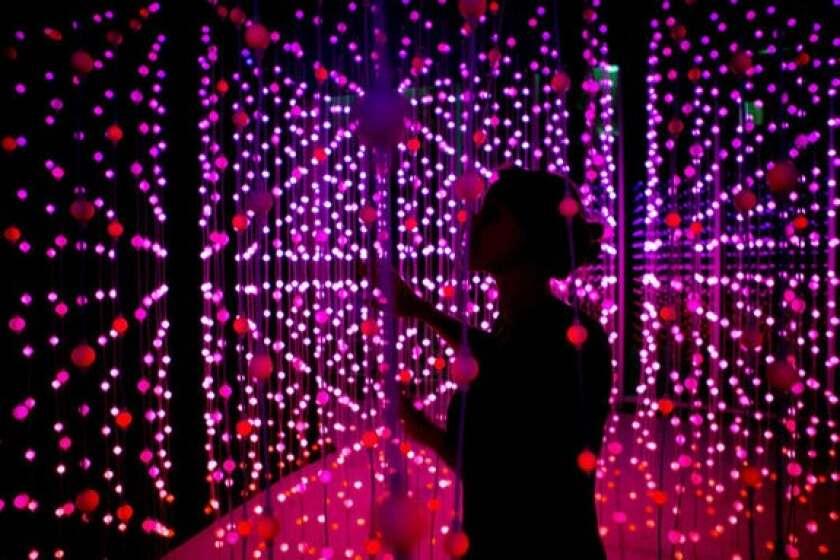 woman in a dark room light exhibit