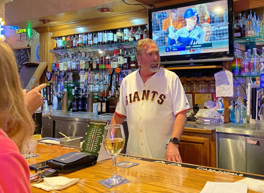 Gary Neal, co-owner of West End Bar & Grill in Cambria, watches his Giants beat the Dodgers Friday night.