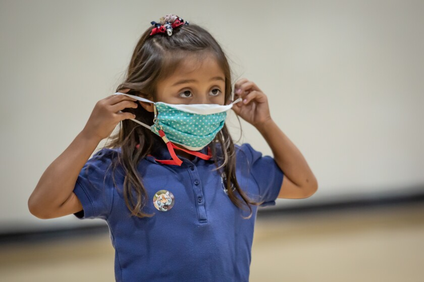 EL CAJON, CA - AUGUST 24: Second grader, Julia puts her mask on during gym class on Monday, Aug. 24, 2020 in El Cajon, CA. (Jarrod Valliere / The San Diego Union-Tribune)