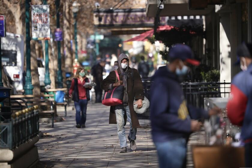 People wearing masks shop in downtown Santa Cruz.