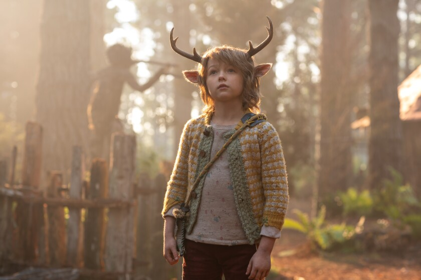 A young boy with deer antlers in a forest