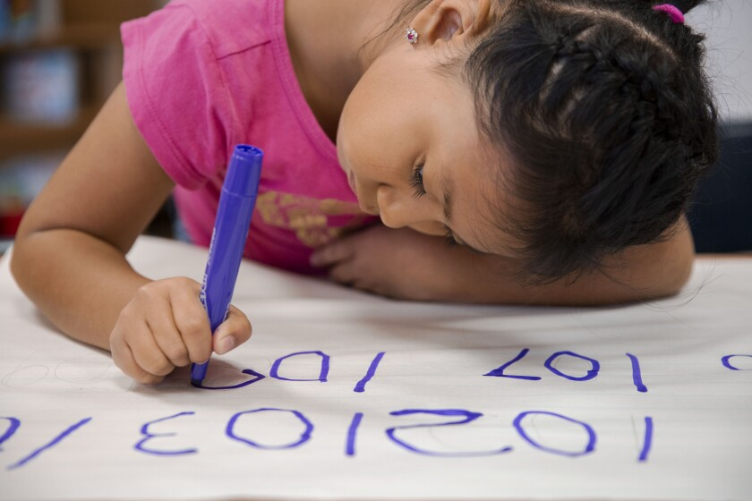 Emily Osorio-Hernandez, 6, writes numbers for a math assignment at Esperanza Elementary School
