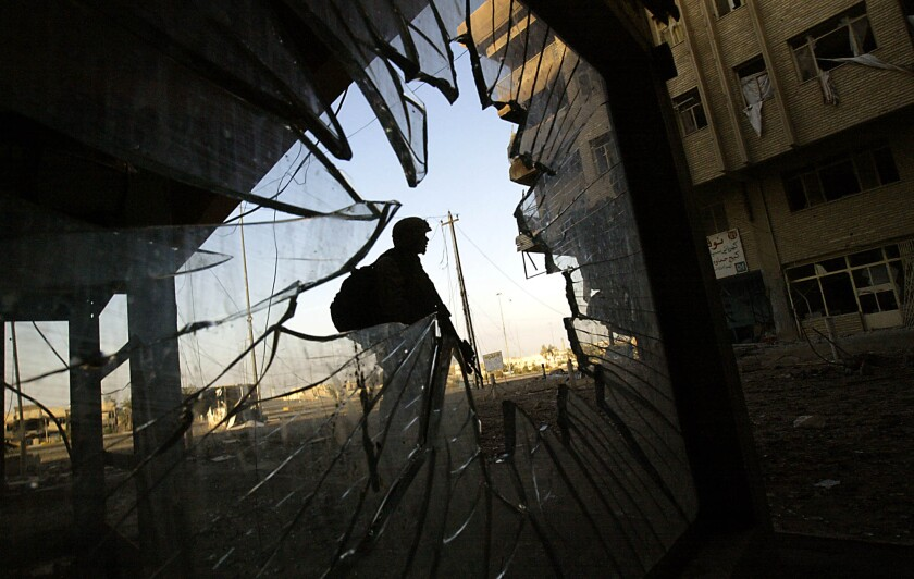A Marine stands guard, seen through a hole in shattered glass