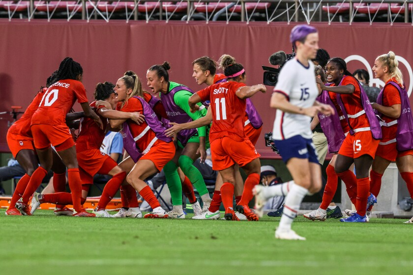 Canada players swarm midfielder Jessie Fleming after she scored on a penalty kick against the U.S. on Monday.