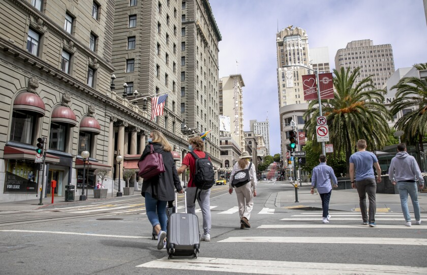 Pedestrians with suitcases walk through union square in San Francisco.