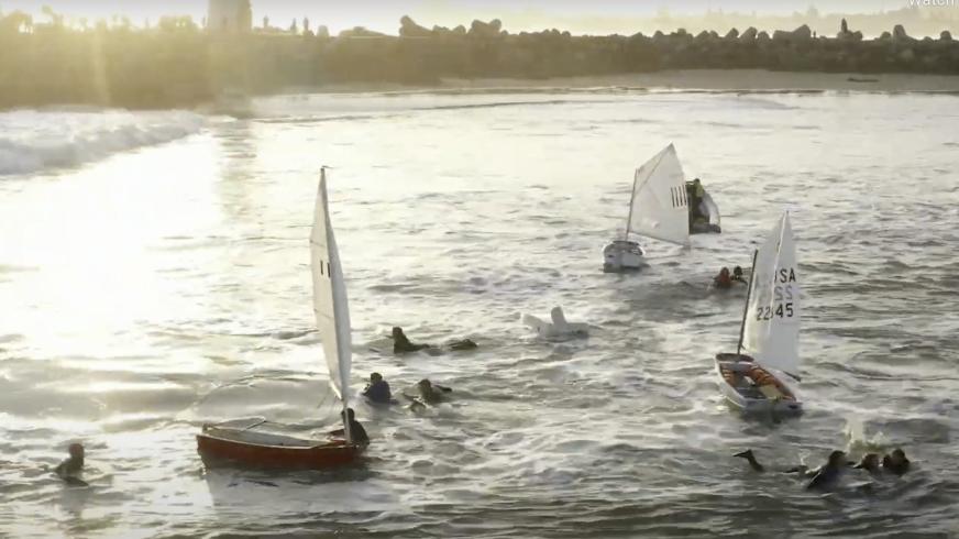 Surfers race toward young, capsized sailors at the mouth of Santa Cruz Harbor on Sunday.