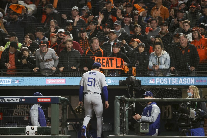 San Francisco Giants fans hold signs and cheer while Los Angeles Dodgers relief pitcher Alex Vesia leaves the game