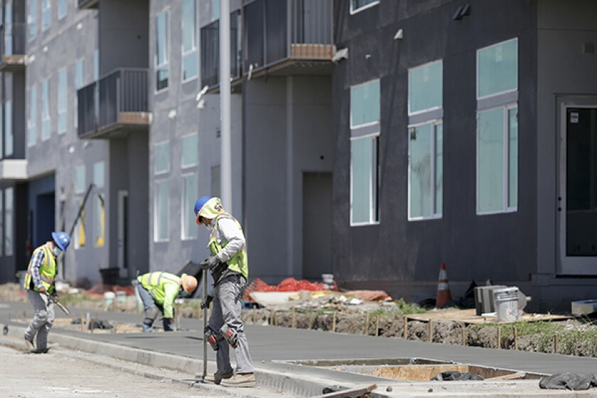 A construction crew works on a 290-unit transit-oriented mixed use affordable housing community