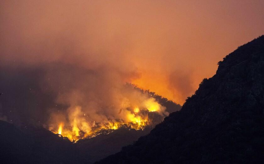 September 15, 2021: Flames burn through brush on a hillside near the entrance station to Sequoia National Park