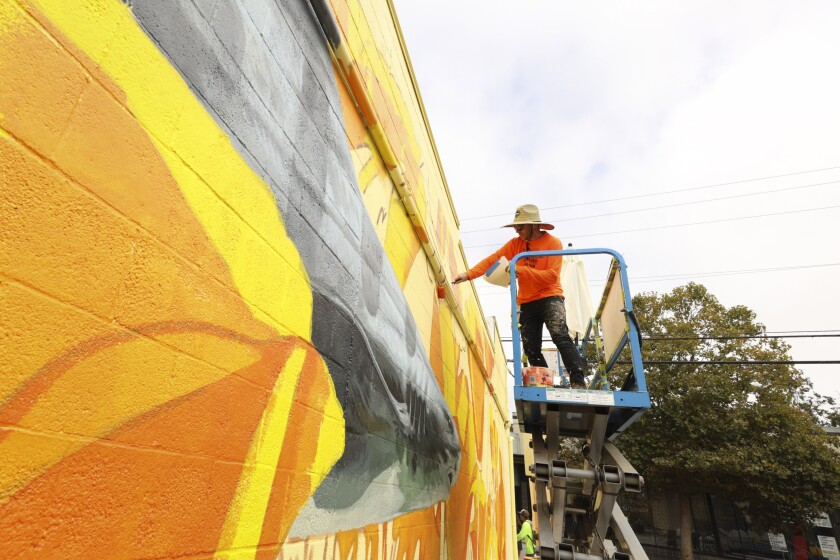 David Rice works on his shark conservation mural on a wall off Front Street.