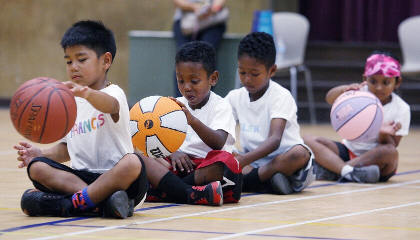 Youth basketball campers sit to dribble the basketball at the annual Tony Pasarella basketball camp at Pacific Park Coummunity Center gymnasium in Glendale on Thursday, July 27, 2017.