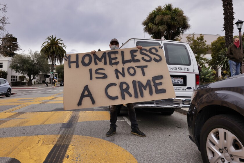 """An activist holds a """"Homeless is not a Crime"""" sign, in front of City Hall on Tuesday night"""