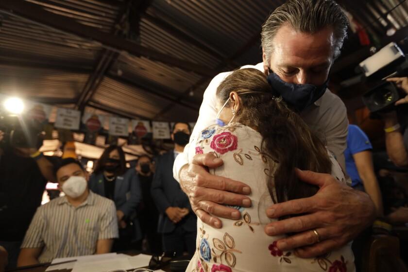 California Gov. Gavin Newsom gives a hug to a volunteer who works the phone banks.